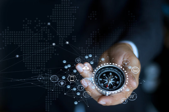 Businessman with a compass holding in hand. Define marketing direction and  search customer global network