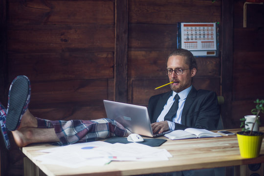 Freelance wearing business jacket, shirt and pajamas trousers. Man at home office holding legs on wooden desk while working with laptop. Toned image.