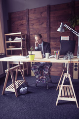 General view of freelancer working at home. Male in business suit having phone conversation, under table legs in home trousers. Toned image.