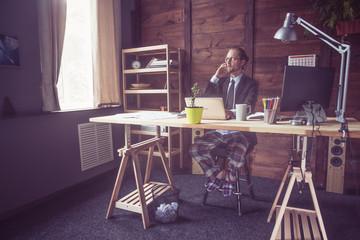Businessman working on freelance at home. View of freelancer wearing jacket, shirt and pajamas pants. Toned image.