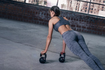 Young woman athlete in sportswear push ups with dumbbells