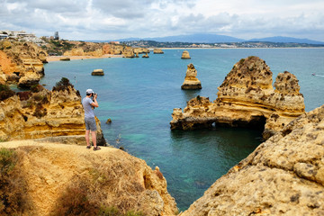 Travel photographer taking pictures of amazing landscape with digital camera while standing on a rock near the Atlantic Ocean in Lagos,  Portugal