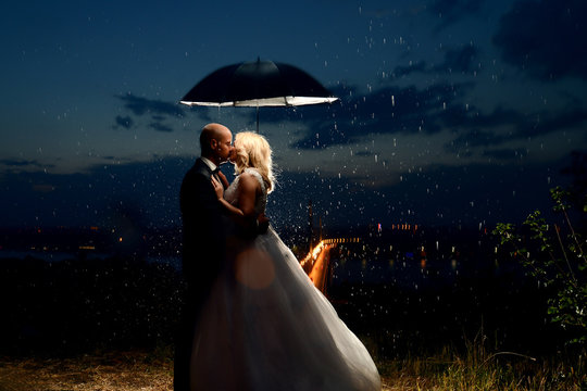 Romantic loving couple newlywed, wedding against background of the night sky. It's raining, the groom and the bride are standing, in love under umbrella.