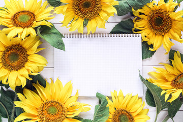 Empty open notebook surrounded by bright sunflowers. Space for text.