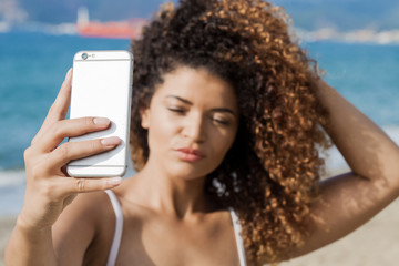 Young woman portrait taking selfie near the sea