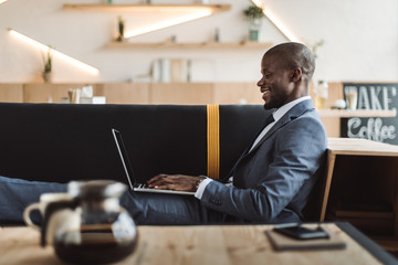 smiling handsome african american businessman working with laptop in cafe