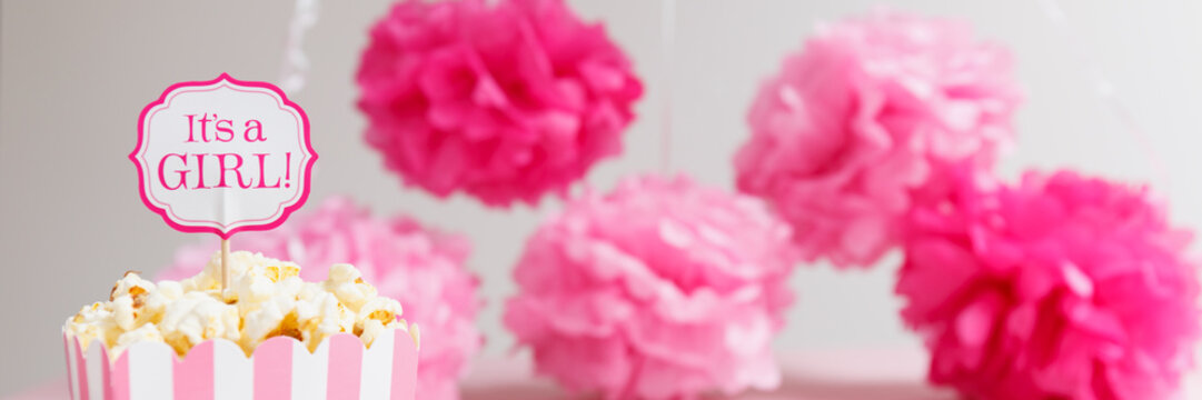 It's a girl sign in a popcorn bag at the baby shower party.  Paper flowers background.  Baby shower celebration concept