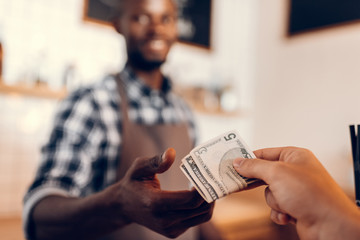 selective focus of african american barista taking cash payment on bar counter in cafe