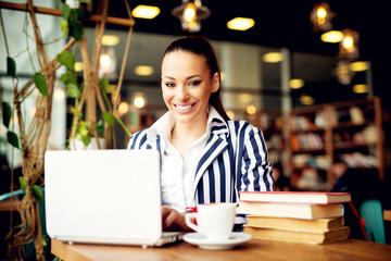 Modern pretty businesswoman having a coffee break and using her laptop.