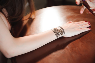 Artist applying henna tattoo on women hands. Mehndi is traditional Indian decorative art. Close-up