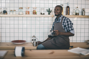 handsome african american barista holding coffee kettle on bar counter in cafe