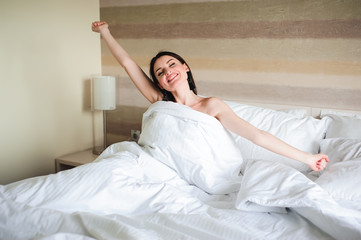 Happy girl waking up stretching arms on the bed in the morning