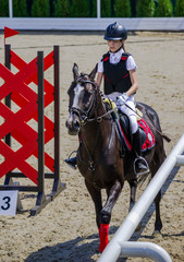 Young girl jumping with black horse. Blond pretty little girl going jump a hurdle in a competition. Girl with crow horse during equestrian showjumping. Bright sunny day.