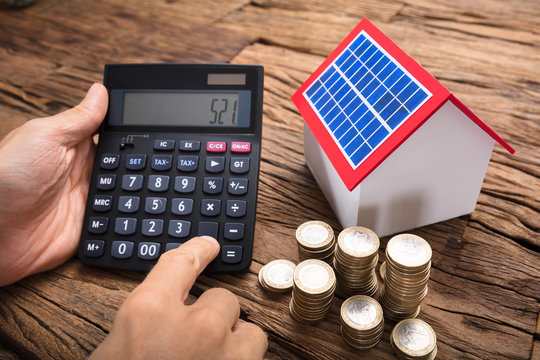 Businessman Using Calculator By Coins And Solar Model Home