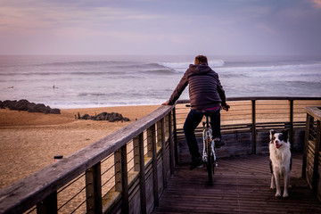Man on a bike and Dog watching the surf from a pier, Hossegor, France