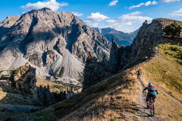 Alpine Mountain bikers ride along a ridge with epic views behind