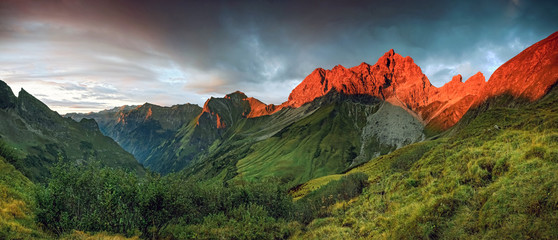 Wall Mural - Amazing sunset and red afterglow in high mountains.