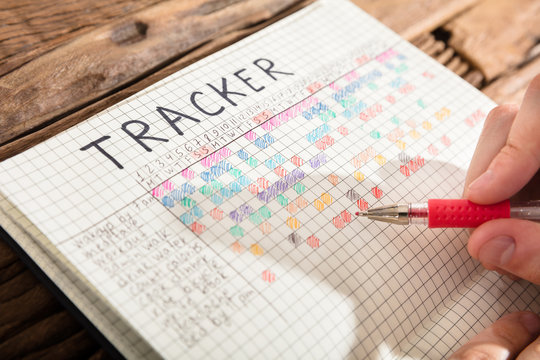 Person Drawing Tracker Chart On Notebook
