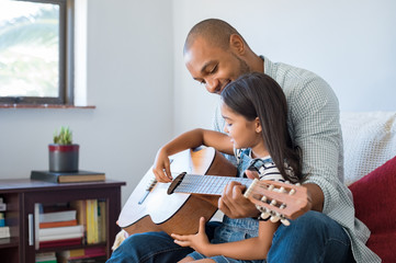 Father playing guitar with daughter
