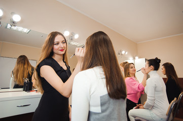 Make-up artist doing professional make-up of young woman
