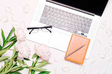 Workplace with laptop glasses notebook pen and peony flowers