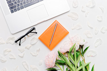 Workplace laptop glasses notebook pen and peonies