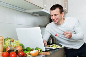 Portrait of smiling guy sitting with notebook and salad dish
