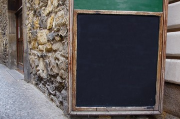 Street black chalk board on the old wall of the cafe