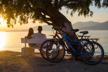 A couple of lovers watching the sunset sitting on a bench by the sea.
