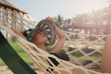 Portrait ofHappy smiling woman enjoying summer dy in hammock on the beach. Holidays, relax and vacation concept