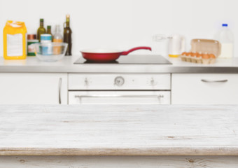 Wooden table in focus over blurred baking ingredients on kitchen