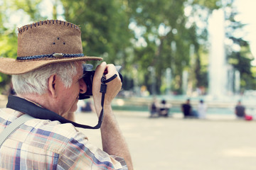 Senior pensioner tourist in hat photographing in vintage style