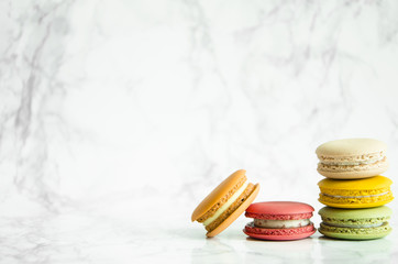 Delicious French colorful macaroons lie on a marble table