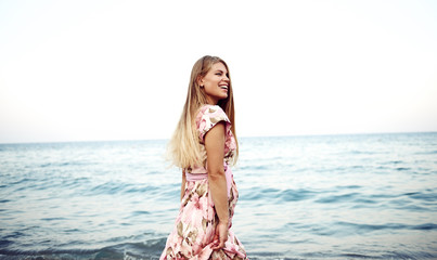 Summer holidays and travel concept. Young attractive woman walking on the beach in floral dress enjoying sunset.