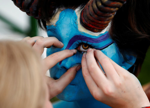 """An artist touches eye lashes on a model during the """"World Bodypainting Festival 2017"""" in Klagenfurt"""