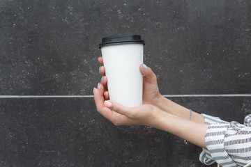 Female hands with a paper cup with coffee