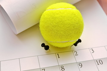 sheet monthly calendar with paper pins holding tennis ball on wooden table close up