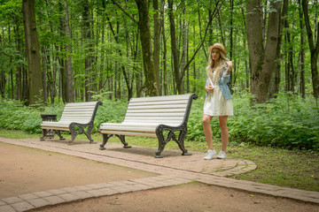 Portrait of pretty woman wearing dress and straw hat in summer warm weather day. Walking at summer park.
