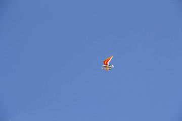 The motorized hang-glider flying in the blue sky