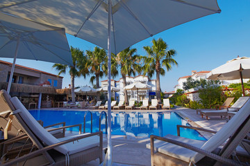 Relaxing pool at small hotel with umbrellas chaise-longue and surrounded with palms