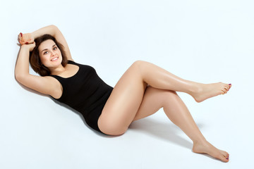 Young woman posing in a black swimsuit lying on a white background