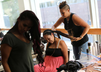 First Nations models get their hair braided prior to preforming at the inaugural Vancouver Indigenous Fashion Week in Vancouver,