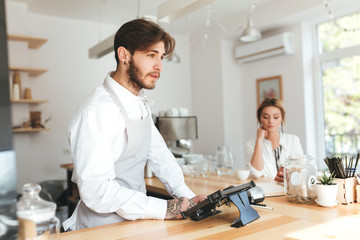 Young pensive barista in apron and white shirt using cash counter in restaurant while thoughtful girl on background sitting at the counter with mobile phone. Cool boy working as barista in coffee shop