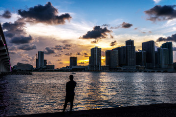 Outline of Boy against Water and Skyline at Sunset