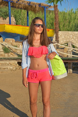 Young girl with sunglasses in bikini has a beach bag on her shoulder