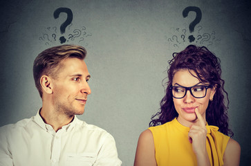 Man and woman with question mark looking at each other with interest