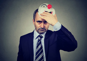 Angry middle aged business man taking off happy clown mask