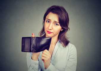 Woman with no money. Sad businesswoman holding empty wallet