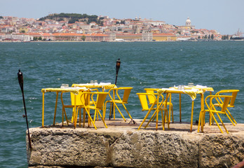 Yellow restaurant tables in the shore of the river Tagus in Cacilhas - Lisbon's cityscape in the background