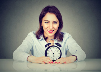 Smiling business woman with alarm clock sitting at table